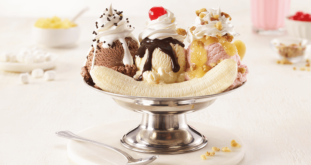 Banana split with one scoop chocolate, one scoop vanilla, ane one scoop strawberry with chocolate syrup, sprinkles and whipped cream in a glass