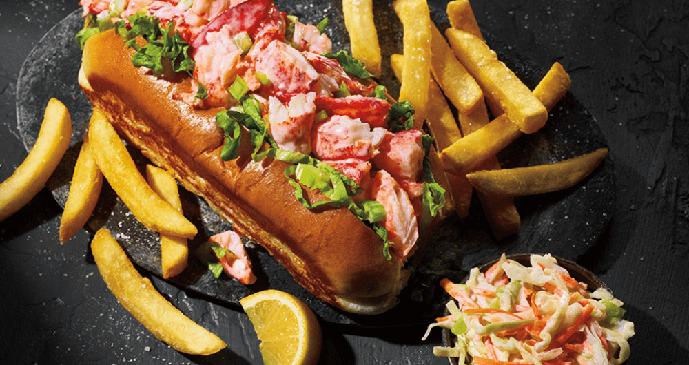 Lobster roll on plate with french fries